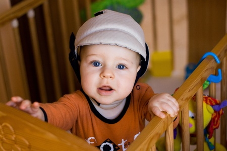 Portrait of the small happy child in a safety helmet standing in the bed photo