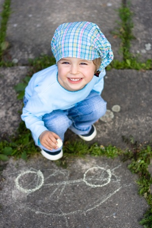 kids drawing: Portrait of cute little girl drawing a car on the ground