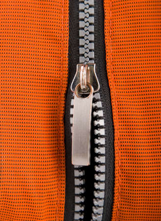 undressing: Close-up of a zipper on vivid orange cloth.