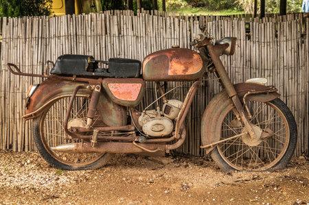 de oude, roestige motorfiets op een straat