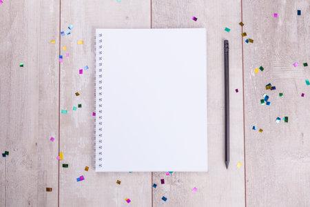 나무 테이블에 빈 메모장과 연필입니다. 위에서 볼