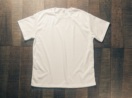 White blank t-shirt on dark wood desk. Stockfoto