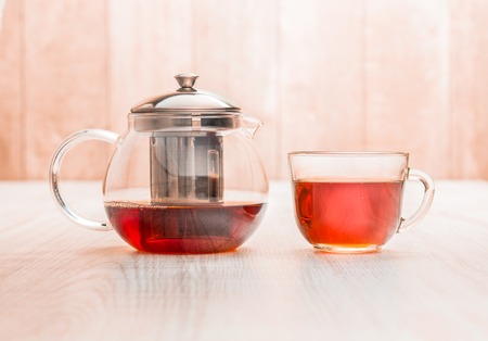 Teapot and cup of tea on wood table background. Archivio Fotografico