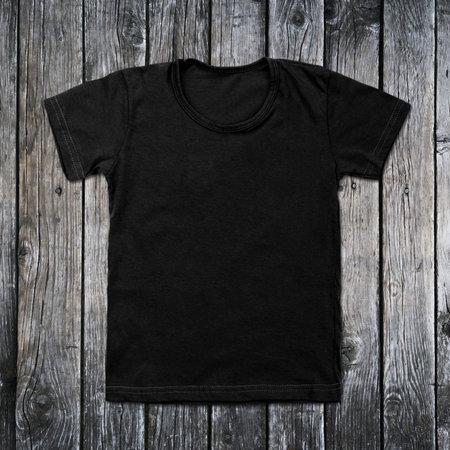 Black blank t-shirt on wooden background. Foto de archivo