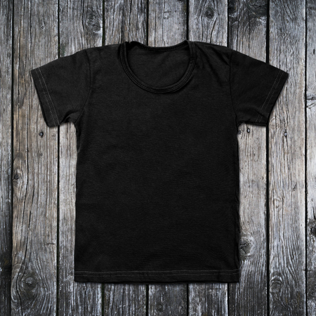 Black blank t-shirt on wooden background. Archivio Fotografico