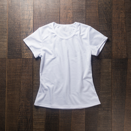 White blank t-shirt on dark wood desk. 版權商用圖片