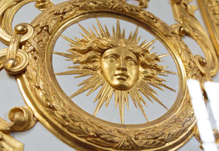 Detail view of golden ornate of Chateau de Versailles depicting human face.