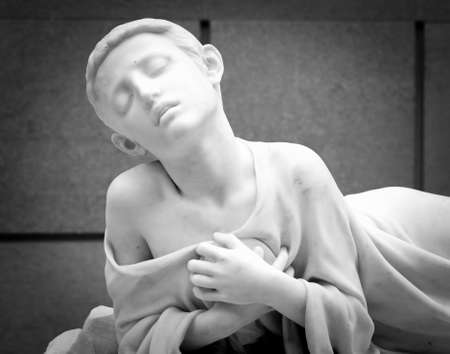 Statue of boy on tomb as a symbol of depression pain