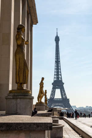 Paris, France, March 27 2017: Golden bronze statues in the Trocadero garden, Eiffel tower in the background