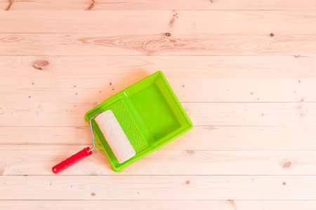 Paint roller brush on wooden table background