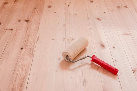 Cepillo de rodillo de pintura sobre fondo de mesa de madera