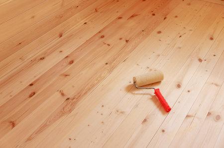 Cepillo de rodillo de pintura sobre fondo de madera