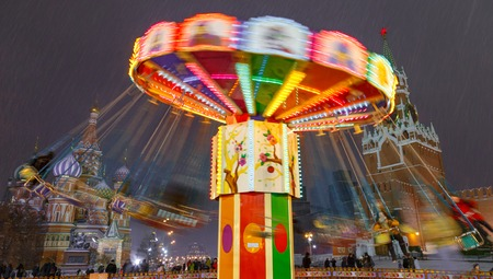 Moscow, Russia, December 5, 2017: Carousel and St. Basil cathedral during Christmas fair area of fair is about 2 thousand square meters