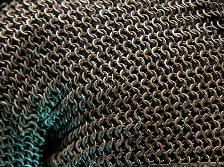 Armor Chain texture. Ring or chain steel mail armour background. Rows of chain mail rings as a texture. metallic silver hauberk from whole rings on a black background close up