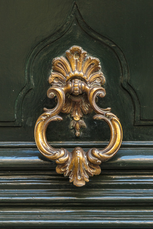 Detail of a bronze metal knocker on a wooden door of house Banque d'images