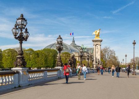 Paris, France, March 31, 2017: Pont Alexandre III in Paris, spanning the river Seine. Decorated with ornate Art Nouveau lamps and sculptures. The most ornate, extravagant bridge in Paris