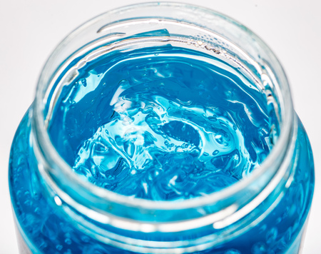 Blue gel container isolated on white background from top view. Transparent gel with bubbles close-up Banco de Imagens