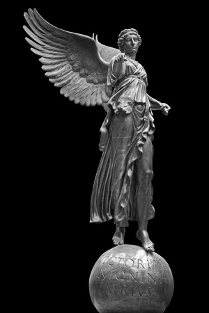 Bronze statue of a Winged Victory. Frontal view of a Statue of the goddess Nike, isolated on black background by clipping path.