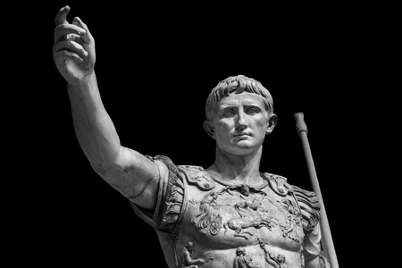 Caesar Augustus, the first emperor of Ancient Rome. Bronze monumental statue in the center of Rome isolated on black background. Фото со стока