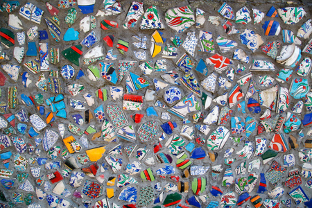 Mosaic of broken tiles wall in Istanbul, wall made of colorful mosaic broken tiles Turkey. Splinters of a white ceramic tile on cement. Texture pieces against a dark background. Mosaic on the wall