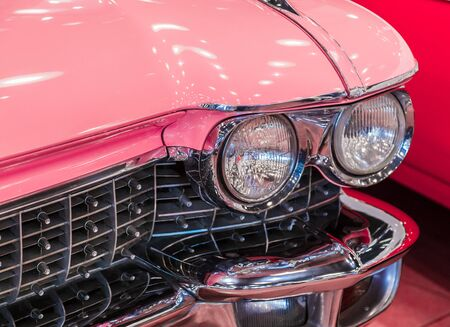 Istanbul, Turkey, 23 March 2019: Close-up photo of pink Cadillac de Ville. Detail on the headlight of vintage classic car. Selective focus. Pink retro car in Rahmi M. Koc Industrial Museum