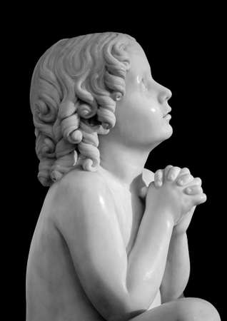 Boy statue pray to God with hands held together. Beautiful old stone statue of praying child isolated on black background