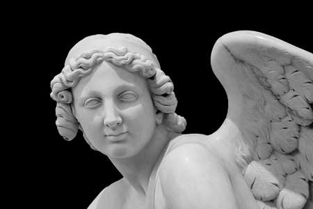 Angel wings isolated on black background with copyspace. Statue of cherub wing close-up 版權商用圖片