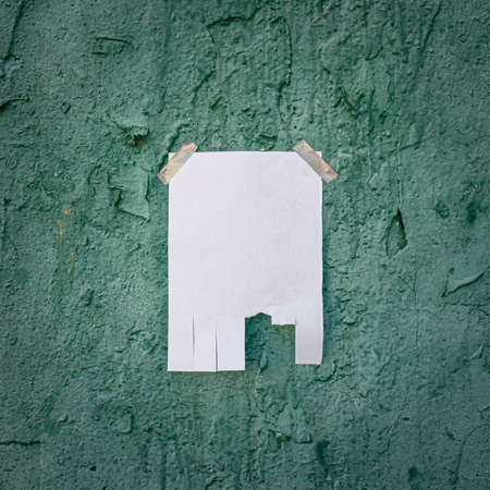 Tear off paper on paint wall. Mock up template. Street paper ad or announcement with tear-off stripes with phone number. Blank design. Copyspace mockup 版權商用圖片