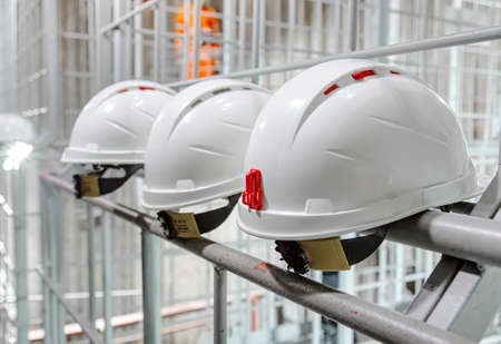 White safety helmets hanging on wall at the factory. Construction engineer safety white headgear