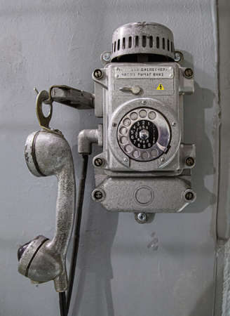 Old metal wall-mounted telephone with rotary dial. Antique phone with dial