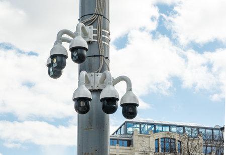 CCTV cameras on one mast against a blue cloudy sky. City CCTV
