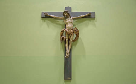 Christian background with crucifix of Jesus Christ on distressed concrete wall with copy space