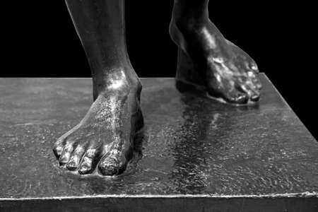 The side view close up detail of ancient man statue on a pedestal with feet toes
