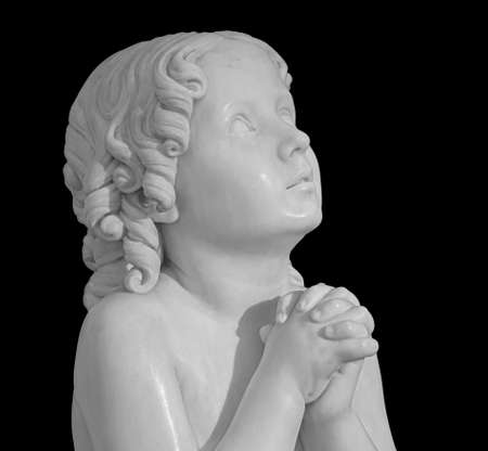 Beautiful marble statue of an pray infant angel isolated on black 版權商用圖片