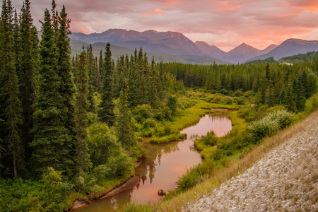 Sunset on the road trip in Yukon territory in Canada, pink and red colors at sunset time, natural beauty