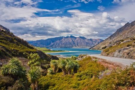 Beatiul blue Hawea lake near town of Wanaka in New Zealand, highway picture of New Zealands mountain landscape, road trip in New Zealand, popular travel destination 写真素材