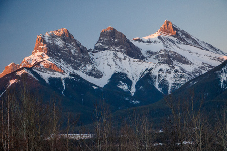 Early spring time in Canmore, snowy mountains, winter atmosphere, icy cold, symbols of town of Canmore, Canada, Three sisters peaks, canadian hiking, canadian nature