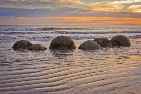 Famous Moeraki Boulders in South Island of New Zealand, touristic place, sunset at coast line