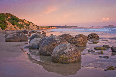 Sunset at th cost with famous rock formation of Moeraki Boulders, NZ, pink sky above touristic popular place
