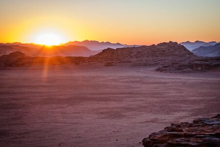 Sunset in Wadi Rum desert in south of Jordan, jordanian main tourist attraction, orange sky during sunset in desert