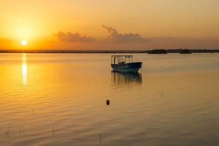 Sunrise above quiet water of Bacalar lagoon in Mexico, boat on the bank of the Seven colors of blue lake 免版税图像