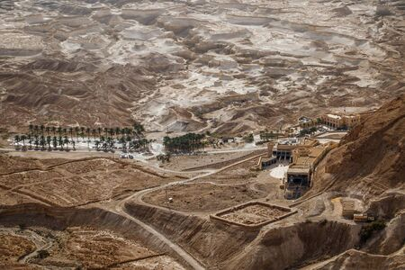 Masada ancient place as touristic attraction with interesting geological surrounding, palm trees along the road in Israel
