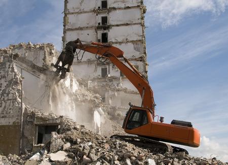Hydraulic crusher excavator demolishing old building photo