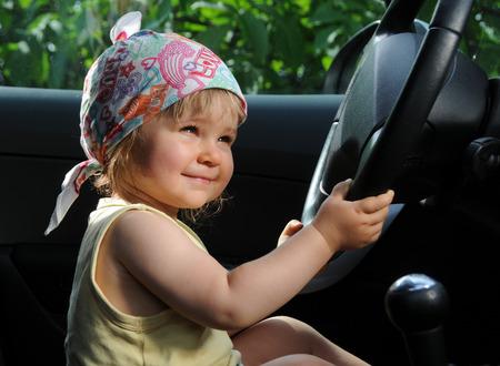 gearstick: Little girl in car hold a steering wheel