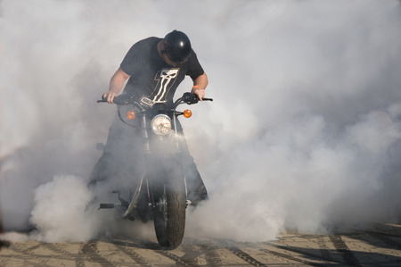 bicycle wheel: WARSAW, POLAND - AUGUST 29, 2015: Biker burning tire and creating smoke. American Day in Warsaw, Poland