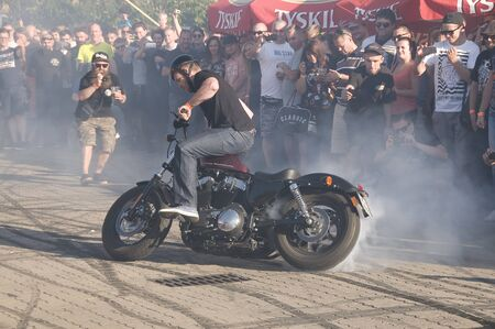 bike tire: WARSAW, POLAND - AUGUST 29, 2015: Biker burning tire and creating smoke. American Day in Warsaw, Poland