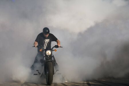 WARSAW, POLAND - AUGUST 29, 2015: Biker burning tire and creating smoke. American Day in Warsaw, Poland
