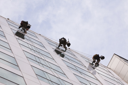 building wall: Climbers wash windows and glass facade of the skyscraper