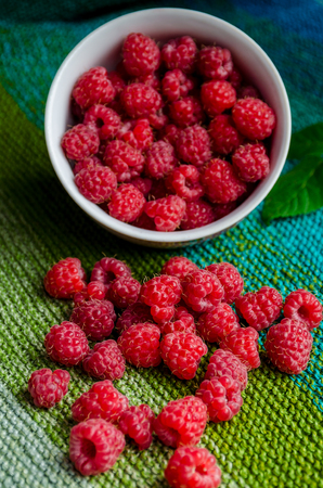 crumbled: plate bent and ripe raspberries crumbled on linen green shades cloth Stock Photo