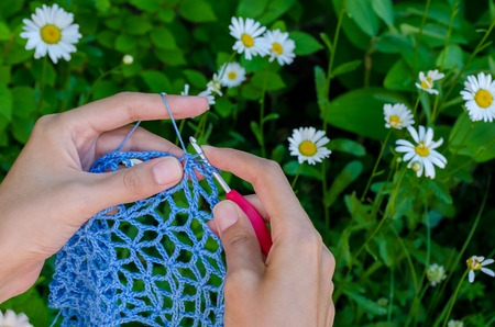 camomiles: female hands crochet blue cotton yarn openwork fabric on a background of green grass and camomiles